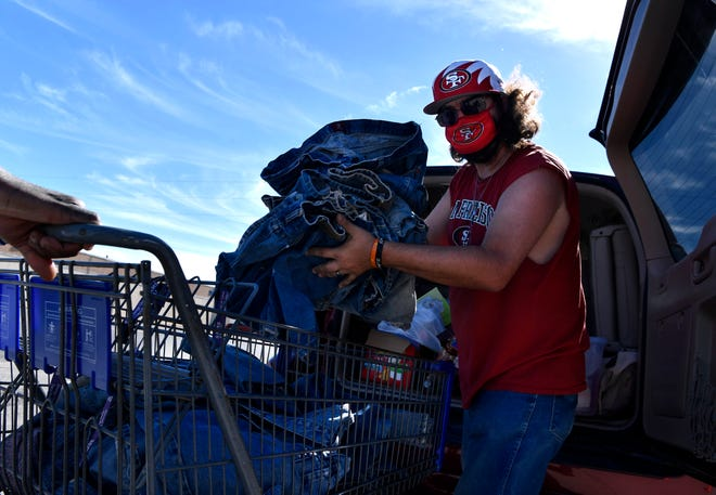 Volunteer Zachary Pruitt loads pants into a shopping cart Tuesday at Love & Care Ministries.