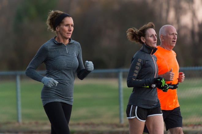 Martha Klueh, left, runs her route around Wesselman Park with friends Miki Fields and Tom Stofleth Thursday evening, Nov. 12, 2020. Klueh has competed in marathons in 49 of the 50 states and will compete in her 50th state, Oklahoma, in early December.