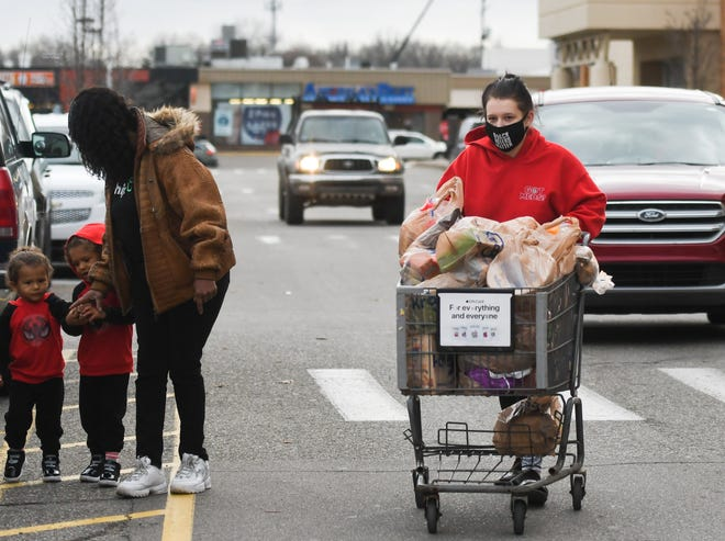 """""""We haven't changed our shopping habits, we're here twice a week and normally buy this many groceries,"""" Alissa Dotson of Lansing says Tuesday, Nov. 17, 2020, seen leaving Kroger in Frandor as her mother-in-law Cya Jackson tends to Alissa's sons Braxston, 2, and Bobby, 4."""