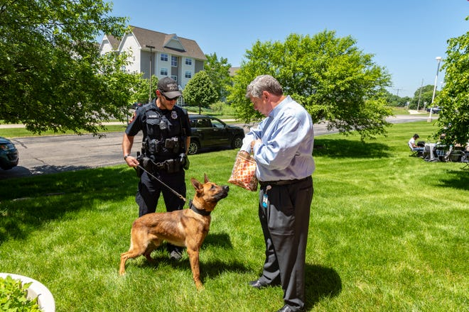 K-9 Szeci and his handler, Middleton Police Officer Howard Statz, greet Sentry Insurance Board Chair, President and CEO Pete McPartland.  Following a workplace shooting near Sentry's office in Middleton, Sentry and its employees contributed $37,000 to the Middleton Police Department's effort to develop a K-9 team.