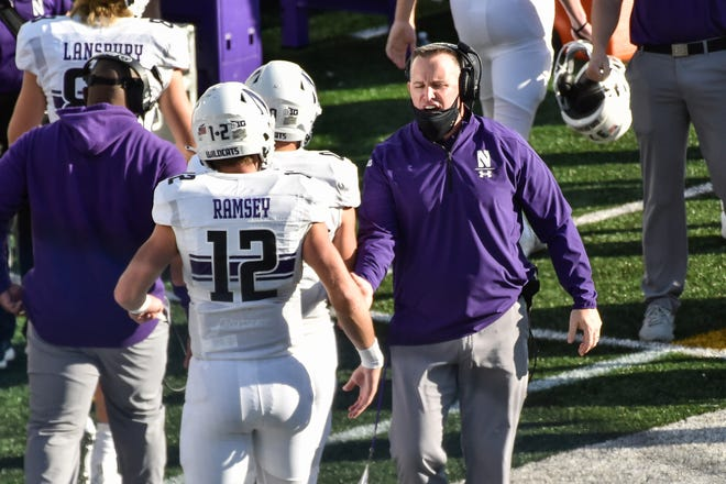 Northwestern coach Pat Fitzgerald celebrates with his team during a game against Iowa at Kinnick Stadium. In an era when the College Football Playoff increasingly features the nation's highest-scoring teams, this year's Big Ten race shows defense still matters.