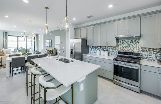 The Hallmark model, now open, features a centrally located gourmet kitchen and cohesive gathering area.