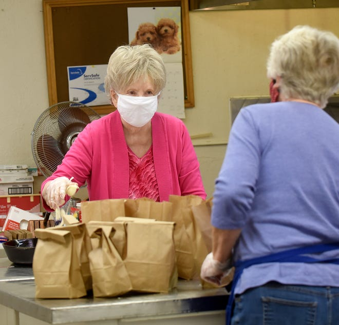 Granville Meals on Wheels longtime director JoAnne Knaack prepares a hot meal while Helen Sunkle packages cold lunches for the 15 people served by the villages food service program. Knaack is retiring the day before Thanksgiving at age 86 after 29 years of food preparation.