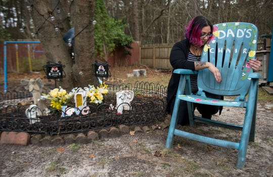Ruth Montan reflects next to a chair that belonged to her father. Santiago Disla Martinez, who died died due to COVID-19 on April 20, 2020, that sits next to a memorial located in the backyard of her Browns Mills home for Montan's father and her uncle Martin Silvero, who died due to COVID-19 on April 19, 2020.