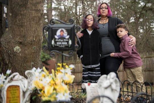 """Ruth Montan stands with her 9-year-old daughter Hannah and 6-year-old son Erick as they reflect next to a memorial located in the backyard of their Browns Mills home for Montan's father Santiago Disla Martinez, who died died due to COVID-19 on April 20, 2020, and for Montan's uncle Martin Silvero, who died due to COVID-19 on April 19, 2020.  Montan said """"It is hard to feel thankful for anything after losing my father and uncle due to COVID-19 this year, but I am thankful for the closeness of my family and for the time we spend together."""""""
