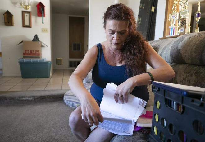 Donna Dale looks at paperwork related to her eviction from her Phoenix apartment at the end of July of 2020, at the home of a family friend where she and her son, Jahnythan Craig, 16, are staying in Phoenix on November 16, 2020. Dale lost her job in mid-March as a server at a restaurant because of the COVID-19 pandemic.