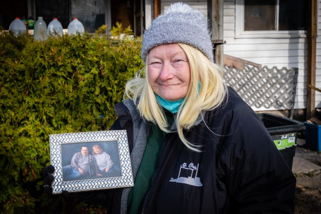 Anna Roberts holds a photo of herself with her husband Bill Tuesday, Nov. 17, 2020, outside their Port Huron home. Bill, who had Parkinson's disease, died when the house caught fire last Thursday.