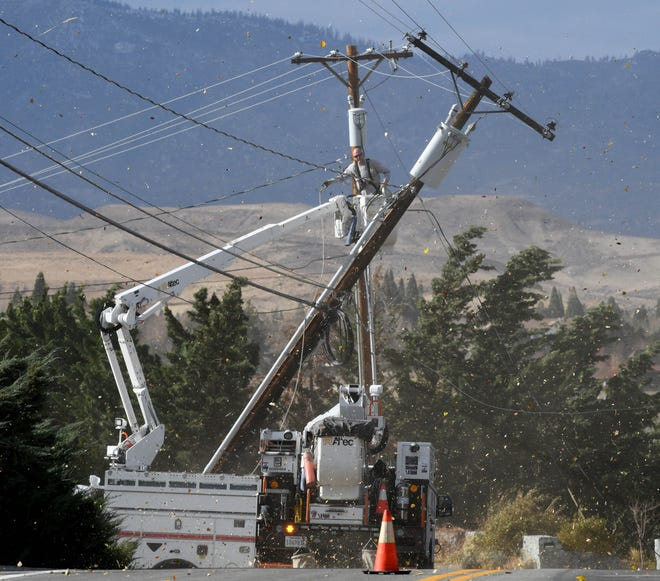As the wind blows leaves througth the air, an electrician works on a power pole that broke during Tuesday high winds on West Plumb Lane on Nov. 17, 2020