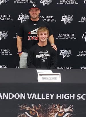 Joe Kolbeck (seated) and head baseball coach Jeremy Van Heel attend a letter of intent signing ceremony at Brandon Valley High School on Thursday, Nov. 12.