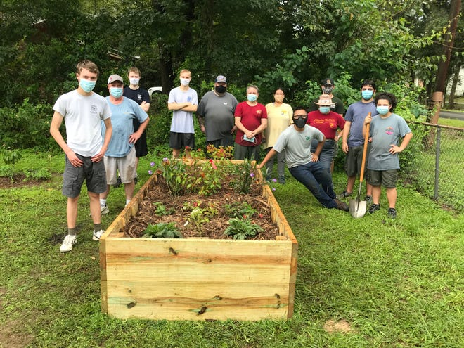 Troop 44 Eagle Scout candidate Titus Etters poses with a team of Scout volunteers, who worked for four hours putting together the two large wooden gardening boxes and planting the 30 native Florida plants.