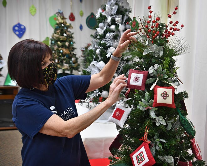 Kris Gossom, executive director of Interfaith Outreach Services, adjusts a cross stitched ornament on the Stitcher's Dream Christmas tree donated by the First United Methodist Church of Holliday for the Oh! Christmas Tree fundraising event.