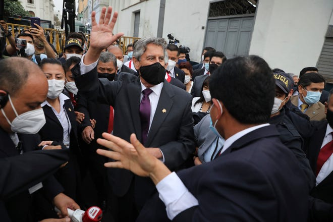 Peru's new interim President Francisco Sagasti waves to the crowd after he was designated by Congress to lead the nation, in Lima, Peru, Monday, Nov. 16, 2020. Congress chose Sagasti to become the nation's third president in the span of a week after Congress ousted Martin Vizcarra and the following protests forced his successor Manuel Merino to resign.