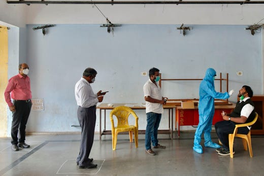A health worker conducts a rapid antigen test for Covid-19 coronavirus on a lecturer at college premises as the state government education department directed the reopening of degree colleges after several months of closure in wake of the coronavirus pandemic, in Bangalore on November 17, 2020.