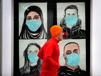 In this Nov. 16, 2020, file photo, a runner passes by a window displaying portraits of people wearing face coverings to help prevent the spread of the coronavirus in Lewiston, Maine. An executive order by Gov. Janet Mills' requires Maine citizens to wear face coverings in public settings, regardless of the ability to maintain physical distance.
