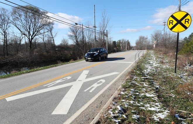 A car crosses an inactive railroad track crossing on Barlow Road in Hudson in November. The track is being eyed for reactivation by a small railroad company, but Akron Metro RTA wants to install a multipurpose trail in the area instead. Hudson City Council will discuss sending a letter of support for the multipurpose trail.