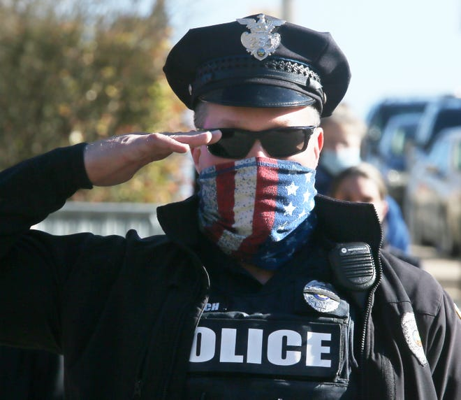 An Akron police officer salutes Wednesday as the procession for Officer Kenny Jones, who died Nov. 7, passes in front of the Akron Police Department.