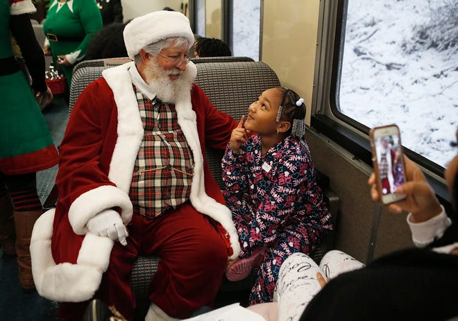 Germani Jones, 6, of Case Elementary thinks about what she wants Santa to bring her while visiting him on the Polar Express on Tuesday, Dec. 12, 2017, at Coventry High School in Akron, Ohio. FirstEnergy and the LeBron James Family Foundation rented the train ride out for Akron third graders in the I Promise program. (Leah Klafczynski/Beacon Journal/Ohio.com)