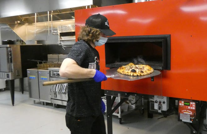 An employee pulls a pizza out of the oven at Ohio Fire, 102 E. Main St.