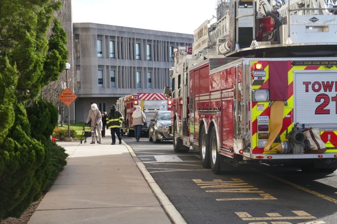 A firefighter assists a person entering the St. Clare Office Building at St. Mary Medical Center Wednesday after firefighters contained a fire in an information technology room in the office building at the hospital complex in Middletown.