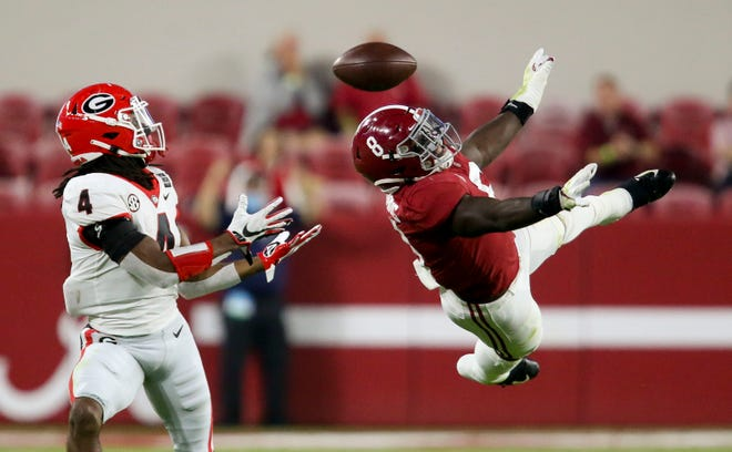 Georgia's James Cook (4) catches a pass that he ran in for a touchdown as Alabama's Christian Harris (8) leaps but can't deflect the ball during a Southeastern Conference game Oct. 17 at Bryant-Denny Stadium in Tuscaloosa, Ala.