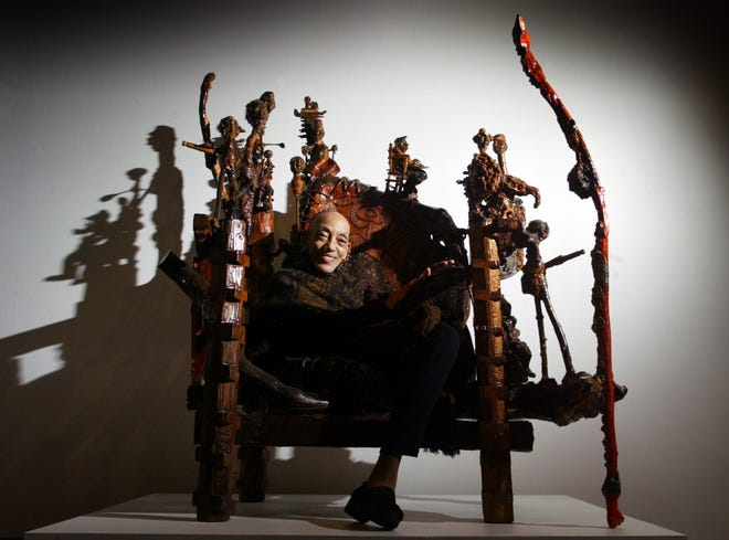 At the Columbus Museum of Art in 2002,  Aminah Robinson sits in a chair she created. The chair is part of a new exhibition at the museum featuring the artist.