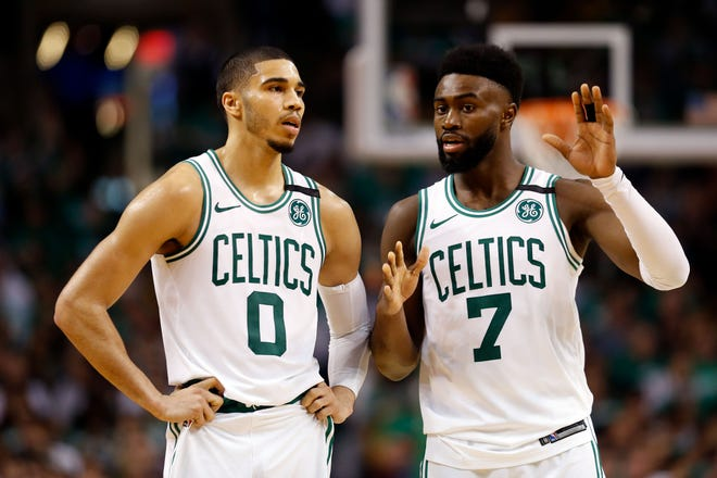 Boston Celtics forward Jayson Tatum (0) and Boston Celtics guard Jaylen Brown (7) talk during the third quarter against the Cleveland Cavaliers in game five of the Eastern conference finals of the 2018 NBA Playoffs at TD Garden.