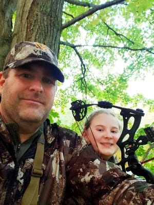 Zane Goucher, left, and daughter Annabelle Goucher pose for a selfie, while bow hunting for deer near Dansville, Mich. Goucher says he hadn't gone hunting in 22 years but took up the sport again because the coronavirus outbreak provided incentive to spend more time outdoors with his children.