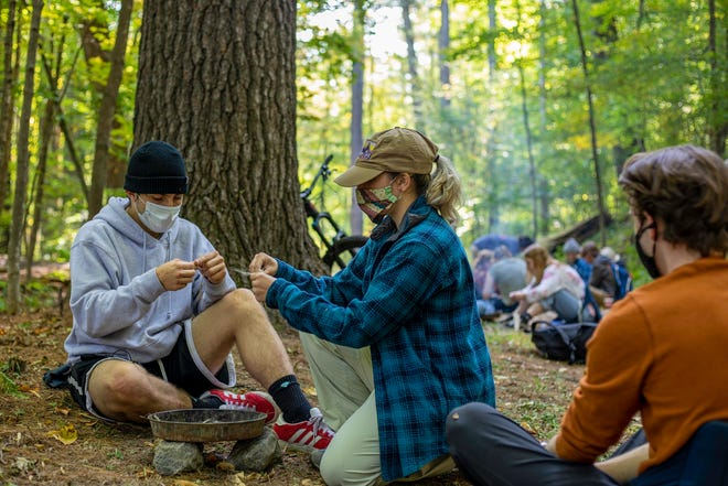 Staci Segalla, center, teaches her fellow students during an outdoor class at Plymouth State University.