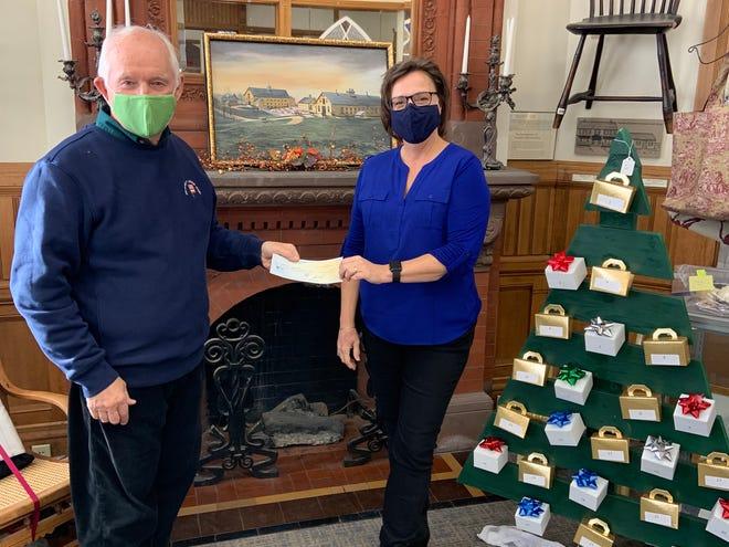 James Kraskouskas, owner of Anthony's Liquor Mart, presents Gardner Museum Coordinator Marion Knoll a check for $2,500.