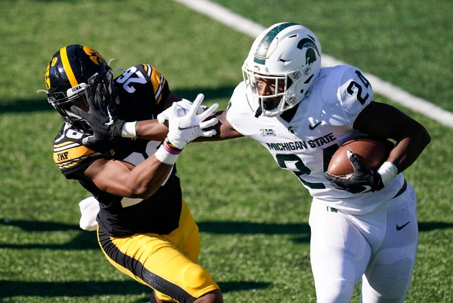 Michigan State running back Elijah Collins (24) runs from Iowa defensive back Kaevon Merriweather, left, during the first half of a game on Saturday, Nov. 7, in Iowa City, Iowa. (AP Photo/Charlie Neibergall)