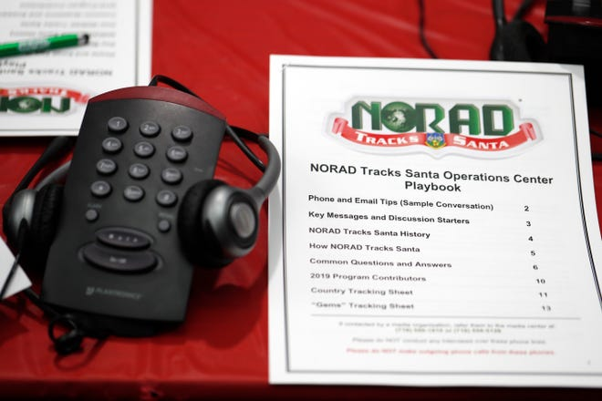 In this Dec. 23, 2019, file photo, a playbook sits next to a telephone set up in the NORAD Tracks Santa center at Peterson Air Force Base in Colorado Springs, Colo. The North American Aerospace Defense Command has announced that NORAD will track Santa on December 24, just as it has done for 65 years. But there will be some changes: Not every child will be able to get through to a volunteer at NORAD's call center to check on Santa's whereabouts, as they have in years before. (AP Photo/David Zalubowski, File)