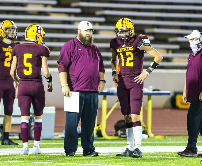 Bells head coach Dale West and senior defensive back/ receiver Tanner Carter talk strategy during the Panthers' bi-district win against Edgewood.