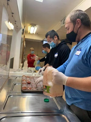 Volunteers from Hope's Kitchen work during a meal service on Oct. 31.