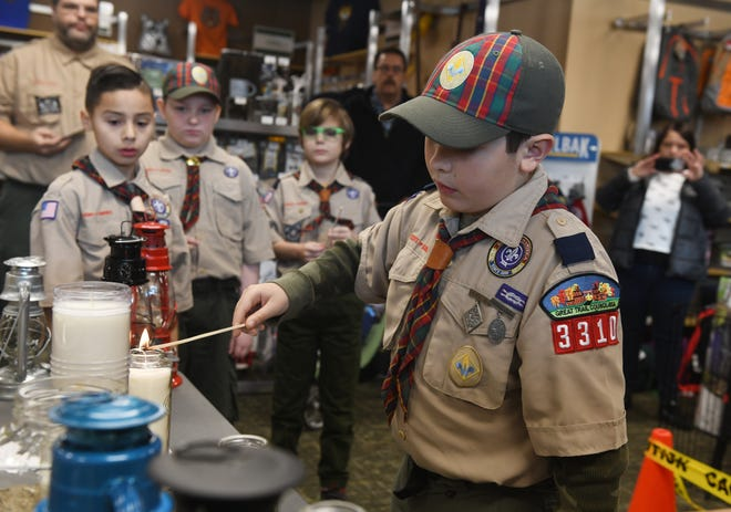 The Peace Light flame, symbolic of the Light of Christ, will come to the Scout Shop Nov. 28. The light is available to groups, individuals and churches. Cub Scout Troop 3310 member Ren Parado transfers the flame at last year's ceremony.