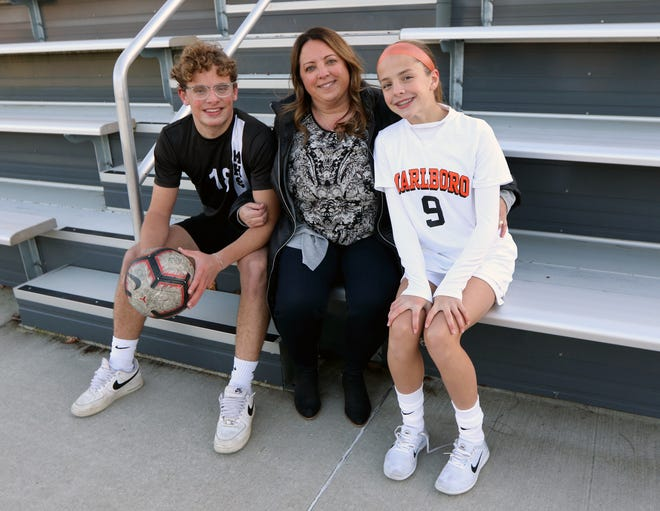Marlborough senior Joey VanBuskirk, 18 (left) committed to play soccer at Southern New Hampshire University and his sister Ava, 14 (right), who made the school's varsity soccer team as a freshman, pose with their mom, Pam, at the Whitcomb Middle School, Nov. 18. Pam played soccer, ran track and was a cheerleader at Marlborough High when she was growing up.