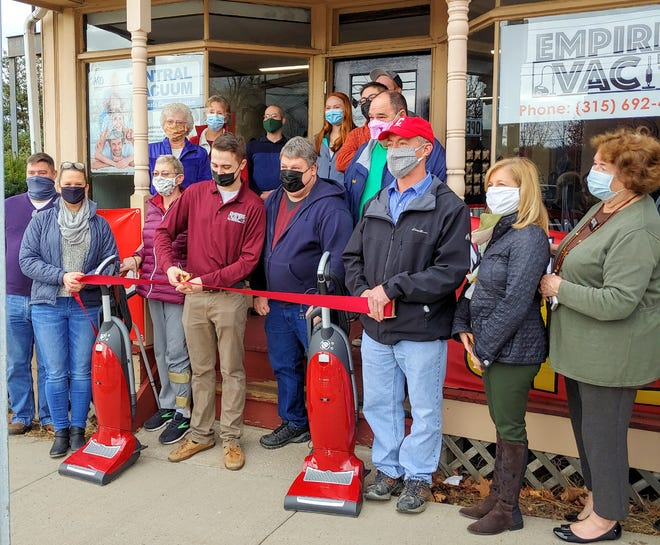 Gregory Palmer, center, cuts the ribbon held by parents Christine and Doc Palmer Nov. 14 to open his second Empire Vac Store in Manlius. They were joined in the ceremony by members of Manlius Chamber of Commerce.