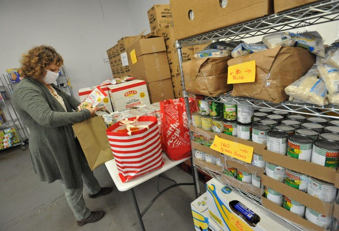 Weymouth Food Pantry Executive Director Pam Denholm packs a Thanksgiving meal that will be distributed to families in need at the Weymouth Food Pantry, Wednesday, Nov. 18, 2020. Tom Gorman/For The Patriot Ledger