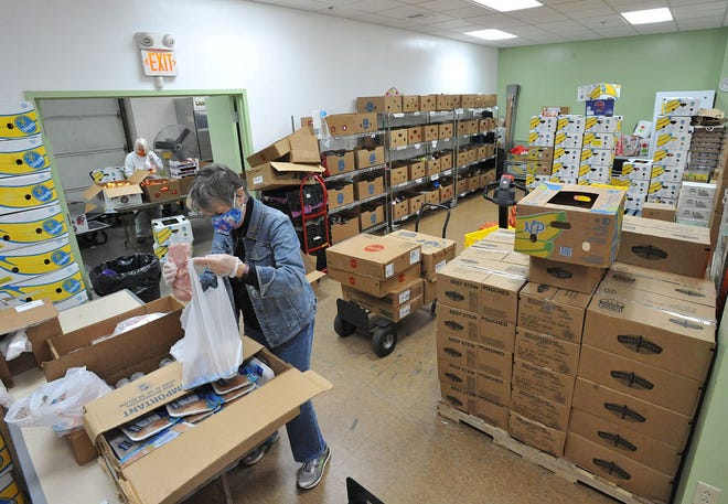 Weymouth Food Pantry volunteer Paule Foster of Weymouth packs Thanksgiving meals for families in need among boxes of fresh fruits and vegetables  at the Weymouth Food Pantry, Wednesday, Nov. 18, 2020. Tom Gorman/For The Patriot Ledger