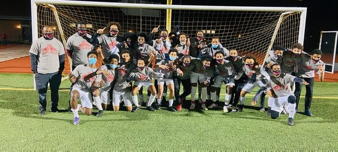 Members of the Brockton High boys soccer team celebrate after winning the Southeast Conference championship with a 3-2 victory over New Bedford on Tuesday, Nov. 17, 2020.
