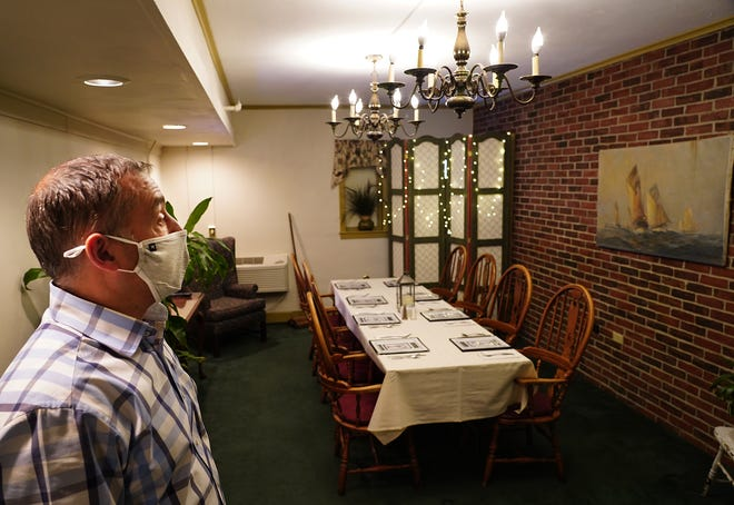 Joe Higgins, owner of the Old Salt and Lamie's Inn on Lafayette Road in Hampton, shows a guest room that has been transformed to a private dining area for 8 people.