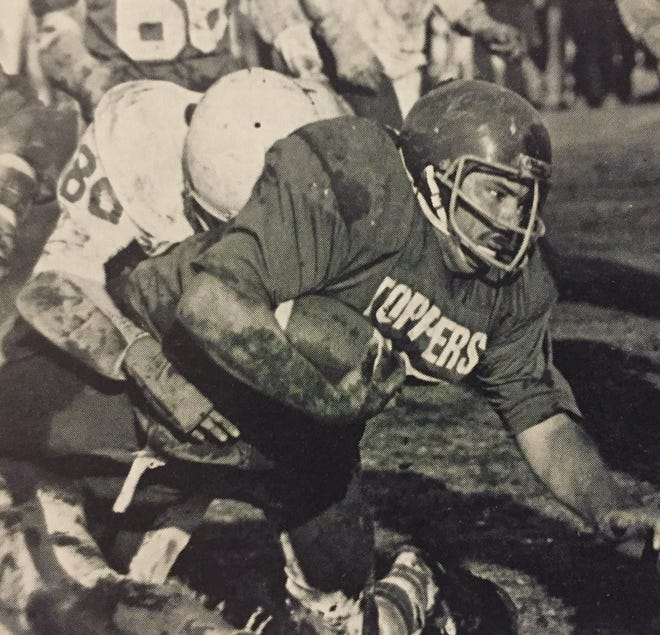 Somersworth fullback Eric Poitras plunges forward in the mud during the 1980 Division II football championship game.