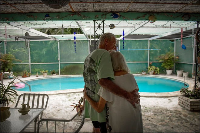 """Sylvia Alexander (86 years old) and her husband William (82 years old) married in 1981 and live in a small home in The Village Palm Springs. Sylvia was diagnosed with Alzheimer's Disease in 2018. The home lacks hurricane shutters and the blown out screens of the lanai allow debris to collect. William rarely ventures out due to fear of falling and all the doors are locked and bolted to keep Sylvia from wandering away.  """"I have memories, she doesn't have many now,"""" said William. [MELANIE BELL/ palmbeachpost.com]"""