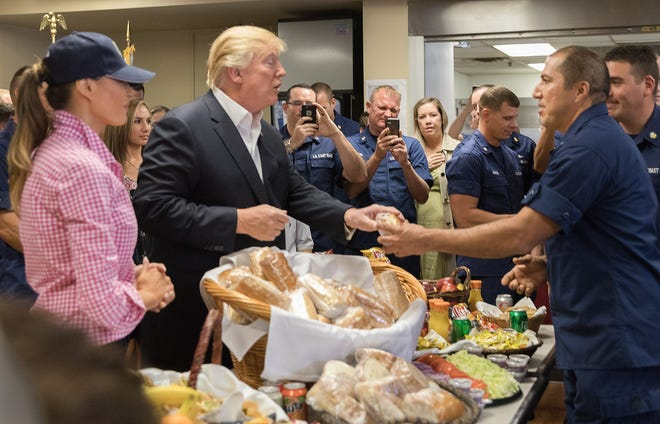 President Donald Trump and first lady Melania Trump hand out sandwiches to members of the Coast Guard during their visit to the guard's Lake Worth Inlet Station in Riviera Beach, on Thanksgiving 2017.