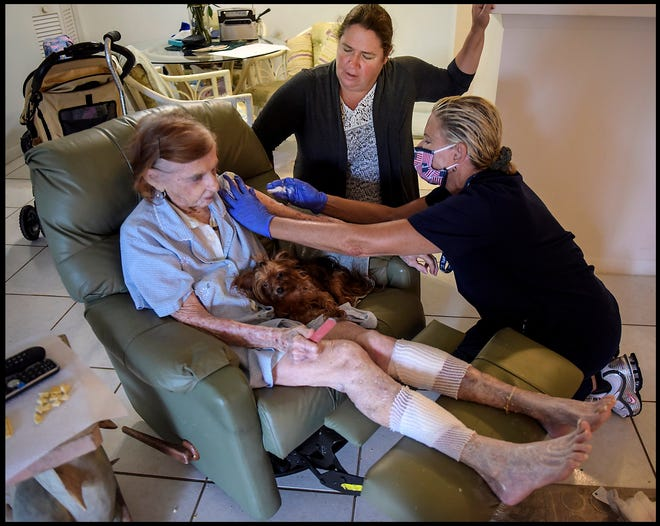 Ruth McBride is 94 years old and lives with her beloved three-year-old Yorkie, Lily, in Palm Beach Gardens. Teri Moran, Executive Director at Connor Moran Children's Cancer Foundation attends to McBride's numerous cancerous lesions as Jennifer Brashear looks on. They remind her that she needs to have them looked at by an oncologist. [MELANIE BELL/ palmbeachpost.com]
