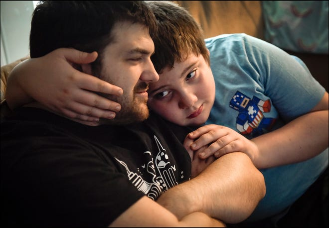 "Caleb Earp, 10, has autism and is nicknamed ""Buggy"" after love bug. He cuddles with his father Christopher who has epilepsy and memory loss. ""I'm a little man with little memory,"" said Earp. Caitlin Earp has a husband with brain damage and epilepsy, an autistic 10 year old son and a 5 year old daughter. [MELANIE BELL/ palmbeachpost.com]"