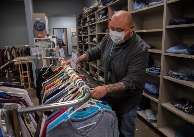 St. Mary's Dining Room staffer Richard Salas stocks clean clothes in the facility's clothing/hygiene center near downtown Stockton.