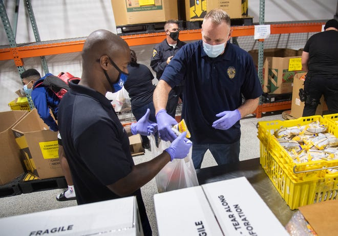 Stockton Unified interim Police Chief Richard Barries, left, and Stockton police Lt. Craig Smith fill bags of food at the Oasis City Center in Stockton to be distributed to the needy for Thanksgiving.
