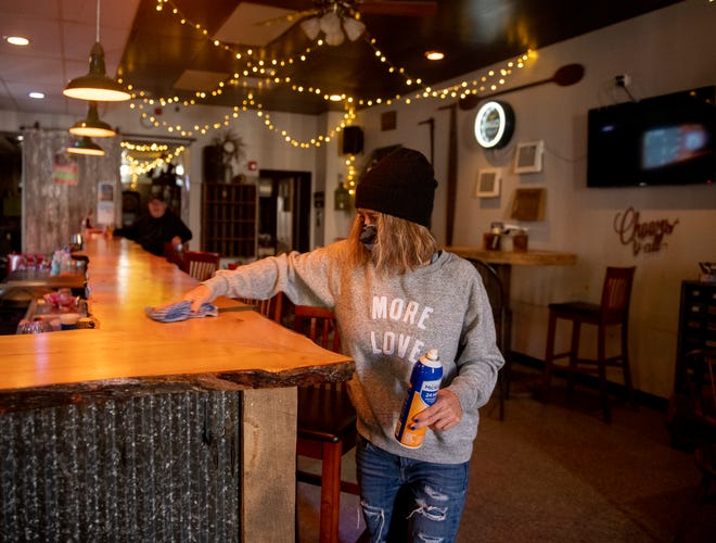 Sandy Knotek, owner of Tavern 1888 in Ravenna, cleans the bar after a customer leaves.