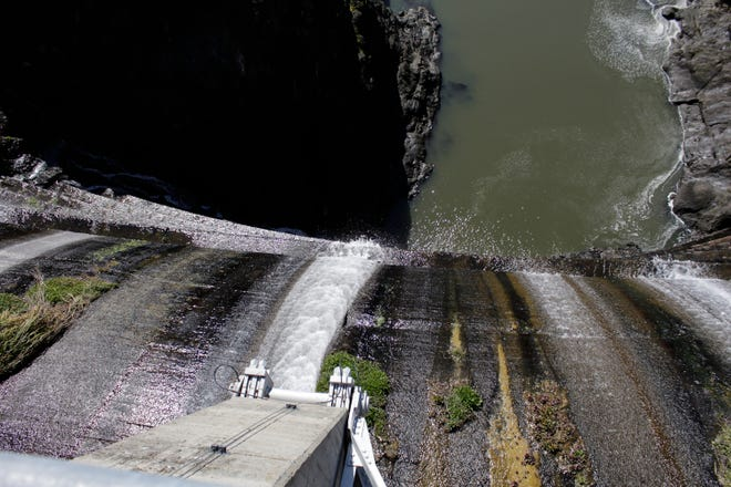 Excess water spills over the top of a dam on the Lower Klamath River known as Copco 1 near Hornbrook, Calif., on March 3, 2020. A new agreement announced Tuesday, Nov. 17, 2020, promises to revive faltering plans to demolish four massive hydroelectric dams on a river along the Oregon-California border to save imperiled salmon by emptying giant reservoirs and reopening hundreds of miles of potential fish habitat that's been blocked for more than a century.