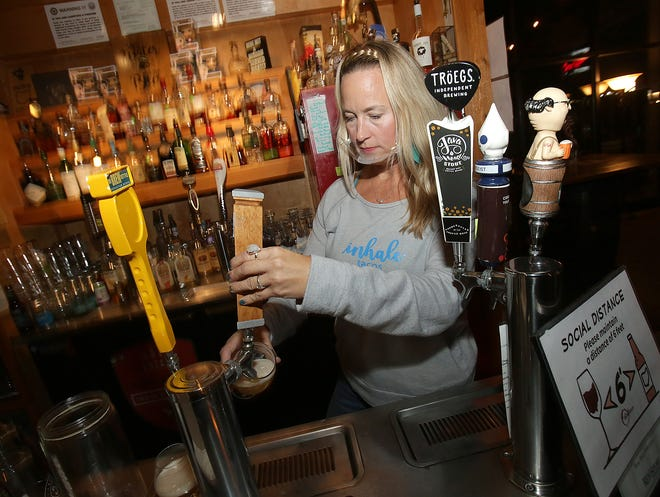 Keri Sullivan, wearing a clear mask, owner of The Barrel Room in North Canton, pours a craft beer for a customer Tuesday.